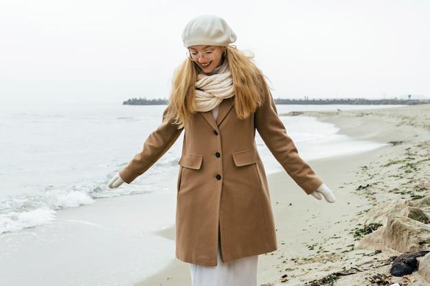 Vista frontal de mulher com luvas na praia durante o inverno