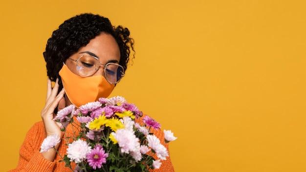 Vista frontal de mulher com máscara e buquê de flores