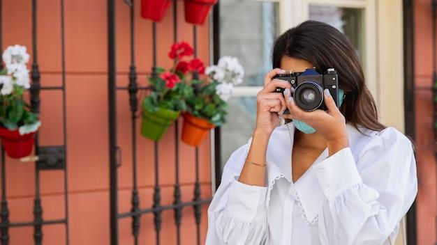 Vista frontal de mulher com máscara facial usando câmera ao ar livre