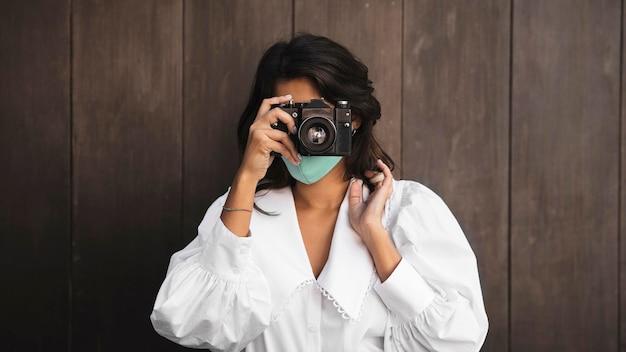 Vista frontal de mulher com máscara facial usando câmera