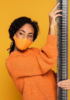 Vista frontal de mulher com máscara posando com moldura