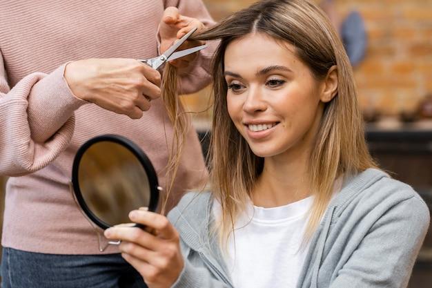 Vista frontal de mulher cortando o cabelo e se olhando no espelho