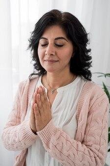 Vista frontal de mulher de olhos fechados rezando