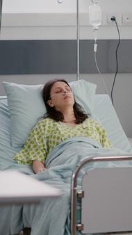 Vista frontal de mulher doente adormecendo se recuperando após recuperação de cardiologia em enfermaria de hospital durante terapia médica