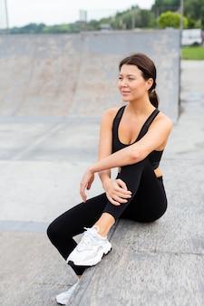 Vista frontal de mulher em athleisure posando ao ar livre