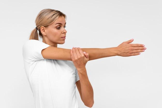 Vista frontal de mulher fazendo fisioterapia com os braços