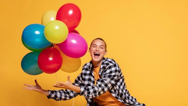 Vista frontal de mulher feliz com balões
