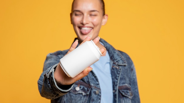 Vista frontal de mulher feliz com lata de refrigerante