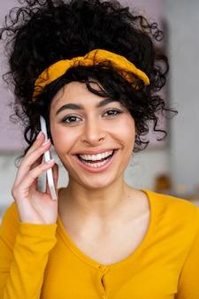 Vista frontal de mulher feliz sorrindo e falando ao telefone