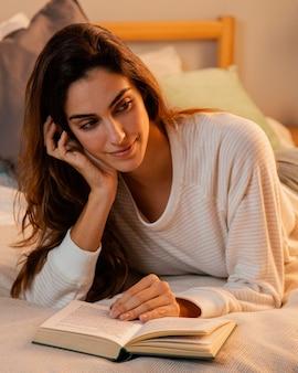Vista frontal de mulher lendo um livro em casa