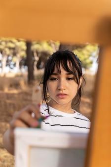 Vista frontal de mulher pintando ao ar livre em tela