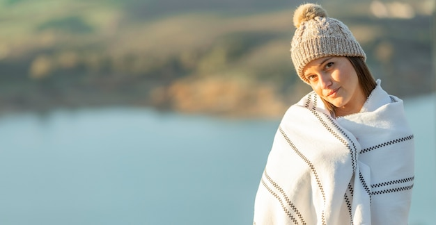 Vista frontal de mulher posando com um cobertor durante uma viagem