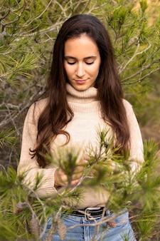Vista frontal de mulher posando na natureza com uma árvore