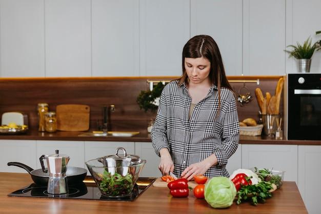 Vista frontal de mulher preparando comida na cozinha de casa