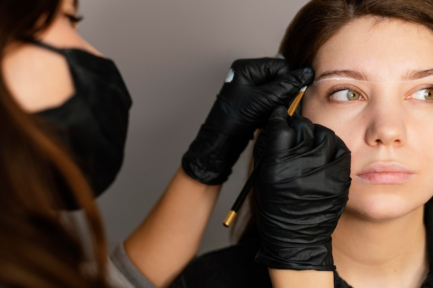 Vista frontal de mulher recebendo tratamento para sobrancelha de uma médica