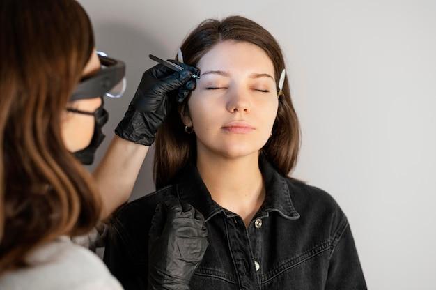 Vista frontal de mulher recebendo tratamento para sobrancelha pela esteticista