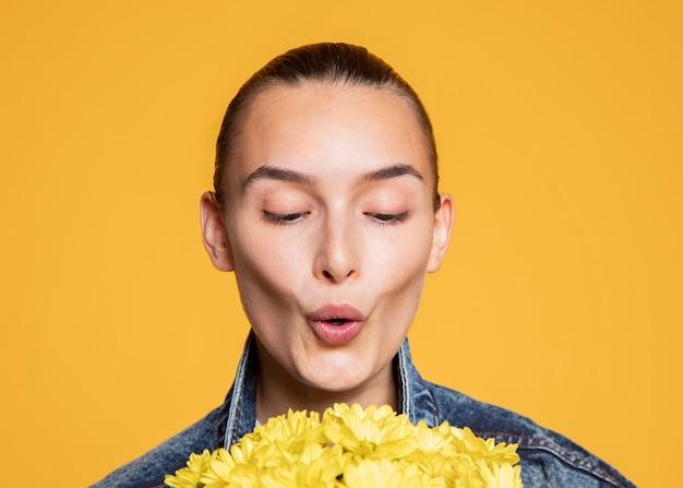 Vista frontal de mulher soprando em um buquê de flores