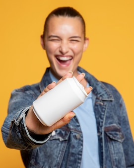 Vista frontal de mulher sorridente com lata de refrigerante