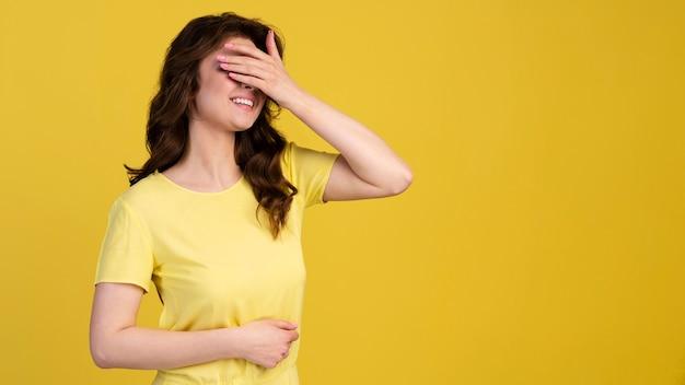 Vista frontal de mulher tímida cobrindo os olhos
