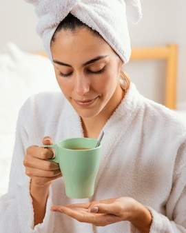 Vista frontal de mulher tomando café em casa após o banho