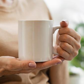 Vista frontal de mulher tomando uma bebida em uma caneca dentro de casa