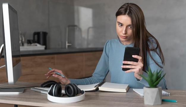 Vista frontal de mulher trabalhando na área de mídia com computador e smartphone