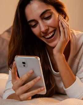 Vista frontal de mulher usando smartphone em casa
