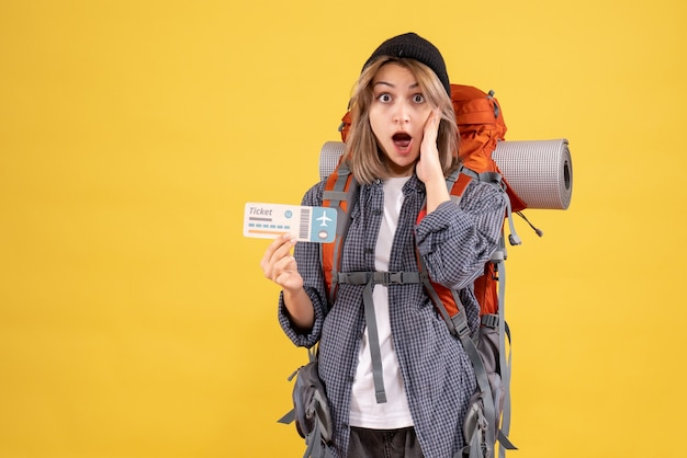 Vista frontal de mulher viajante maravilhada com a mochila segurando o ingresso