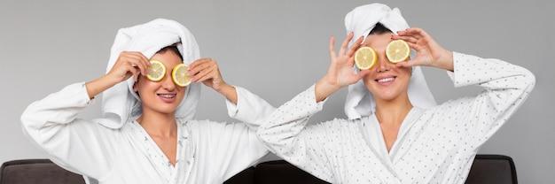 Vista frontal de mulheres em roupões de banho e toalhas segurando rodelas de limão sobre os olhos