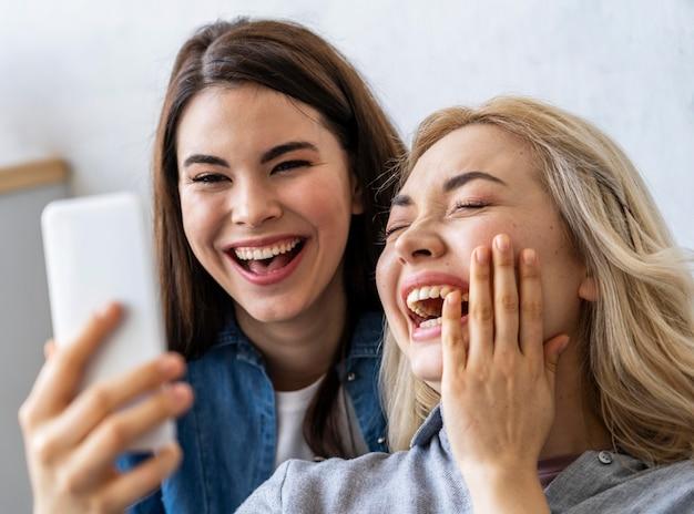 Vista frontal de mulheres felizes sorrindo e tirando uma selfie