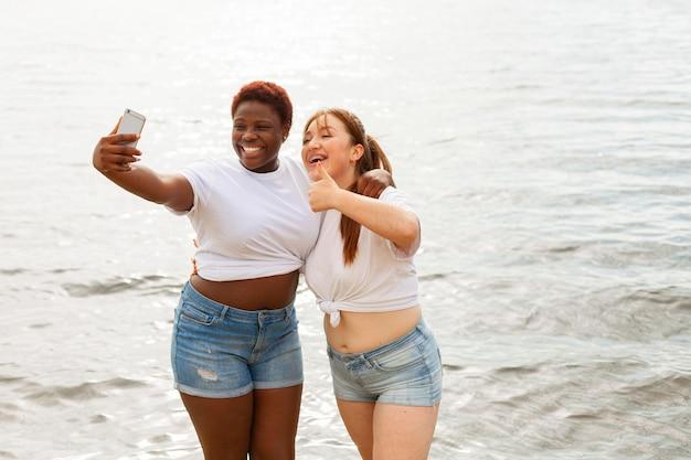 Vista frontal de mulheres felizes tirando selfie na praia