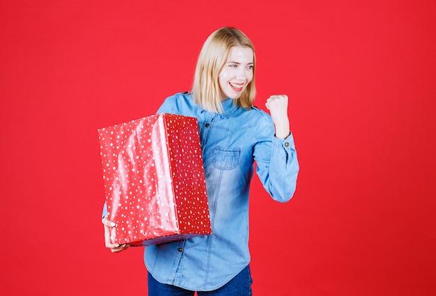 Vista frontal de mulheres jovens de camisa azul segurando uma caixa de presente em uma parede vermelha