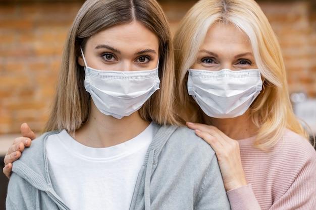 Vista frontal de mulheres no salão com máscaras médicas