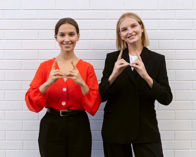 Vista frontal de mulheres sorridentes usando linguagem de sinais