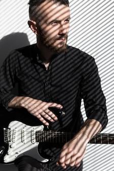 Vista frontal de músico masculino com guitarra elétrica ao lado da janela