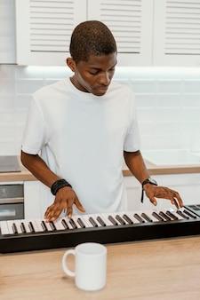 Vista frontal de músico masculino em casa tocando teclado elétrico