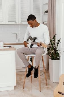 Vista frontal de músico tocando guitarra elétrica