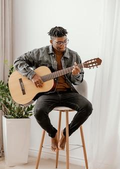 Vista frontal de músico tocando violão em casa
