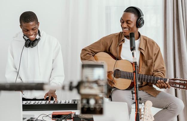 Vista frontal de músicos masculinos em casa tocando violão e cantando