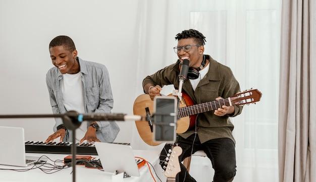 Vista frontal de músicos masculinos sorridentes em casa tocando teclado elétrico e guitarra