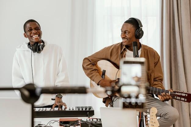 Vista frontal de músicos masculinos sorridentes em casa tocando violão e cantando