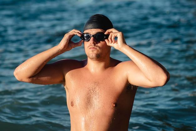 Vista frontal de nadador masculino com óculos de natação e boné