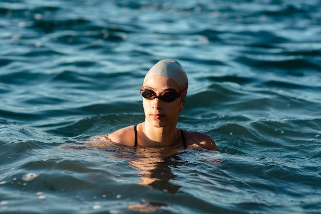 Vista frontal de nadadora com boné e óculos de proteção nadando na água