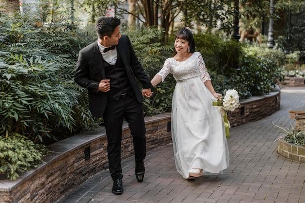 Vista frontal de noivos caminhando pela rua