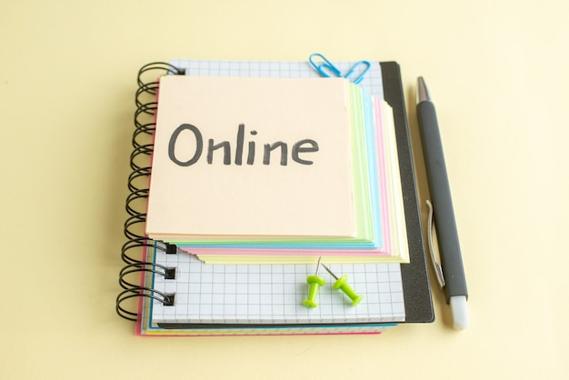 Vista frontal de nota escrita on-line com notas de papel coloridas sobre fundo claro