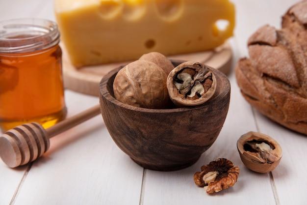 Vista frontal de nozes com queijo, mel e pão preto em um fundo branco