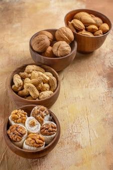 Vista frontal de nozes frescas dentro de pratos em mesa de madeira, porca, amendoim e avelã