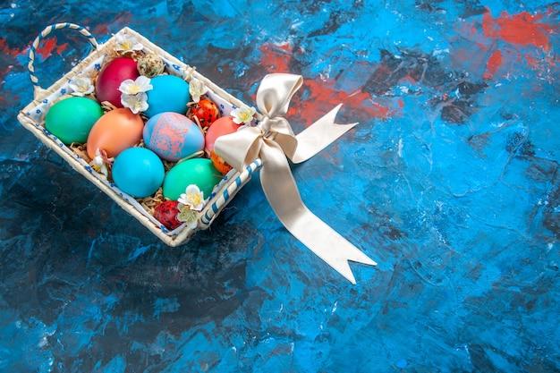 Vista frontal de ovos de páscoa coloridos dentro de uma caixa fofa na superfície azul