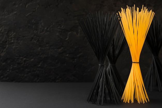 Vista frontal de pacotes de espaguete preto e regular