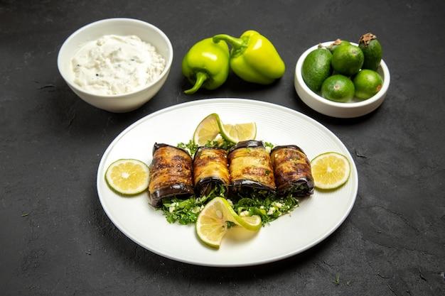 Vista frontal de pãezinhos de berinjela salgados prato cozido com rodelas de limão e feijoa na superfície escura com óleo para cozinhar prato